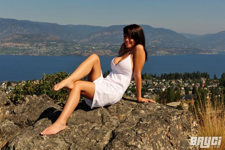 Bryci в белом платье позирует на огромном валуне. Фото 1